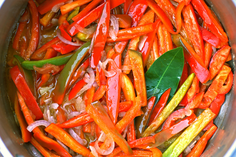 Peperonata - Multi-colored ribbons of sweet bell peppers are stewed with finely sliced onions, tomato and bay leaf in a vibrant sweet and savory dish.