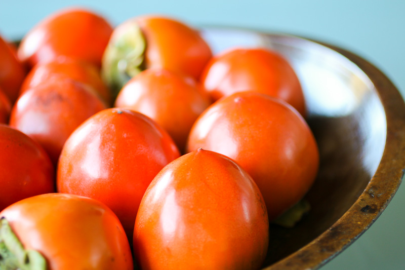 Persimmon and Pecan Bread - Hachiya persimmons in a wooden bowl create a colorful decorative display while they ripen to perfect softness.