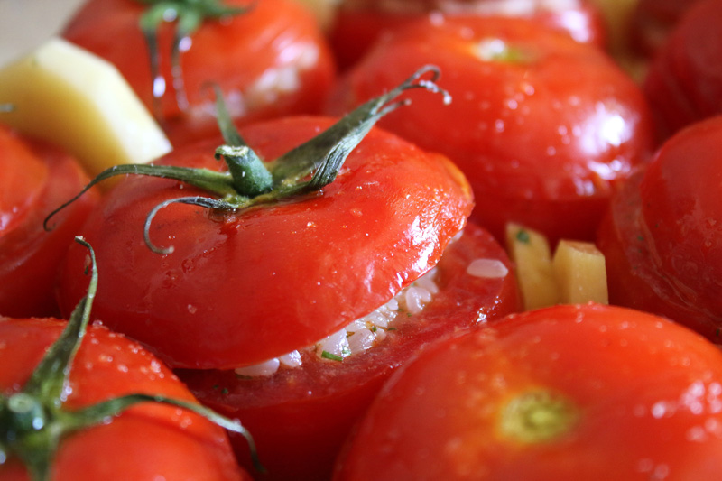 Hollowed out tomato shells are filled with rice and topped with their own red lids before being baked.